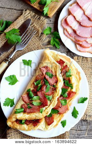 Tasty bacon omelette. Fried omelette stuffed with bacon and parsley for breakfast. Bacon slices on a plate, knife, fork, fresh parsley sprigs on old wooden table. Egg recipe idea. Top view. Closeup
