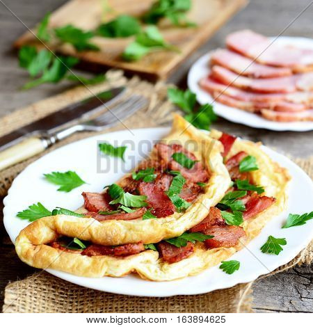 Tasty bacon omelet. Fried omelet stuffed with bacon and parsley for breakfast. Bacon slices on a plate, knife, fork, green parsley sprigs on old wooden table. Egg dish idea. Closeup