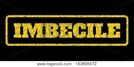 Yellow rubber seal stamp with Imbecile text. Vector message inside rounded rectangular banner. Grunge design and scratched texture for watermark labels. Horisontal sign on a blue background.
