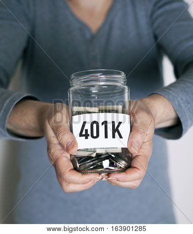 401k plan concept with senior holding money jar