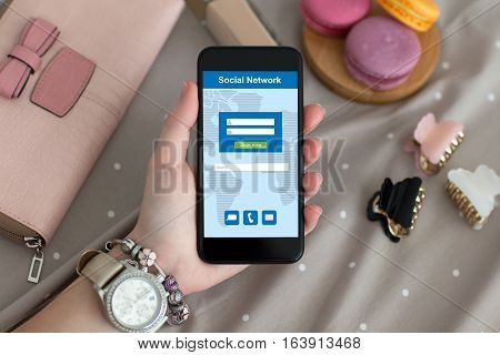 female hand with jewelry and watch holding a phone with social network