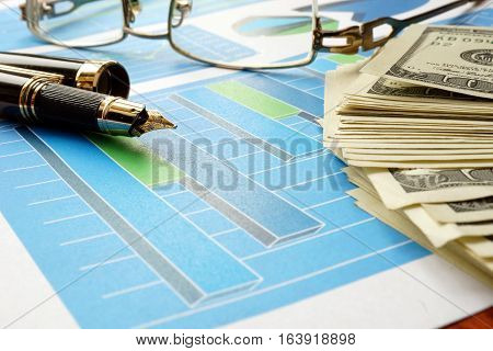 Economical concept. Financial charts  on a wooden surface.