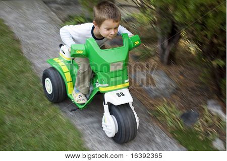 little boy driving  green toy car