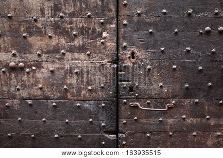 Background: fragment of a wooden door - boards painted in a dark blue red, black, brown color and forged iron nails, door handle, keyhole. Style Medieval Europe (France).