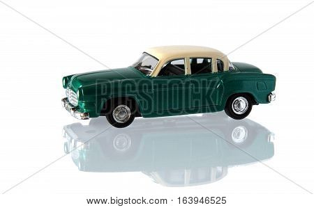 Small green toy car isolated on white with reflection