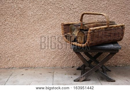 Vintage things: old French garden wooden  folding stool and wicker basket with firewood for the fireplace or stove. background - yellow pink walls. Provence. France.