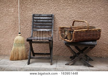 Vintage things: old French garden wooden chair and folding stool and wicker basket with firewood for the fireplace or stove and broom. background - yellow pink walls. Provence. France