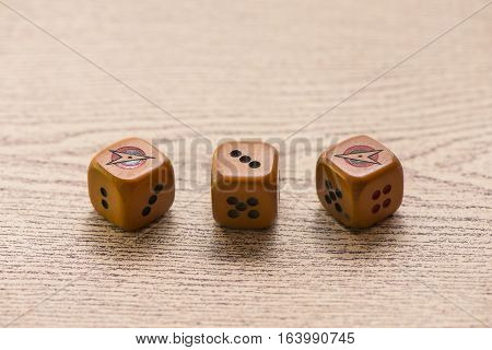 Brown dices on wooden background. Concept of luck, chance and leisure fun./ Sensitive Focus / this dice by handmade