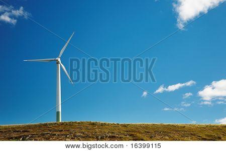 Windturbine op heuvel tegen blauwe hemelachtergrond