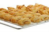 pic of phyllo dough  - Baking grid with rows of fresh baked bourekas aka burek  - JPG