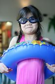 foto of floaties  - Little girl all ready for summer. Goggles pink swimsuit floatie. Humorous expression on face almost like surpressed excitement.