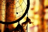 image of dreamcatcher  - native american dream catcher in silhouette against a warm background - JPG