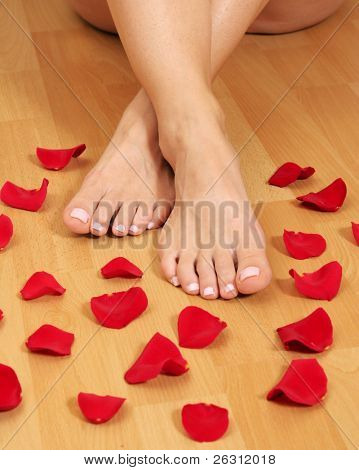 Feet and red rose petals