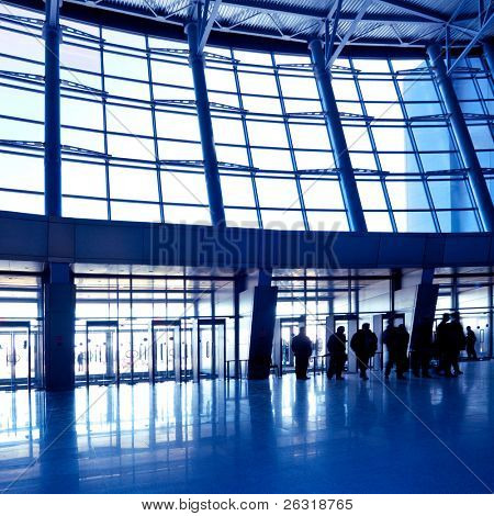 People in wide blue hall window in exposition center, square copmosition