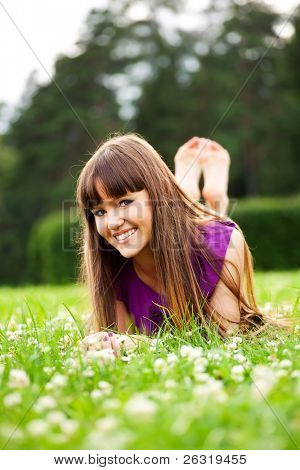 Lying pretty smiling girl with long brown hairs