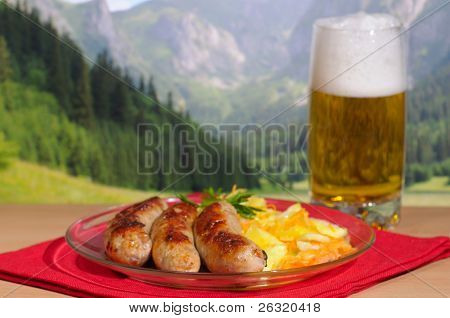 Beer and sausages against mountains