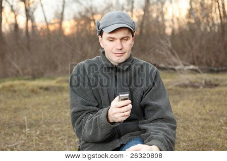 Man with mobile phone in spring forest