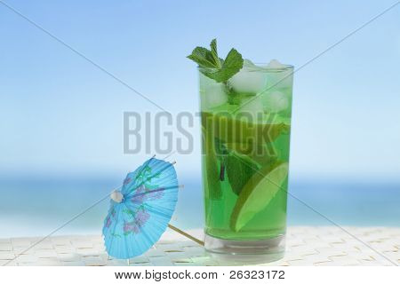 Mojito cocktail in the highball glass against the sea