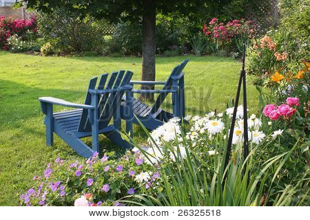 View of backyard garden with two lawn chairs.