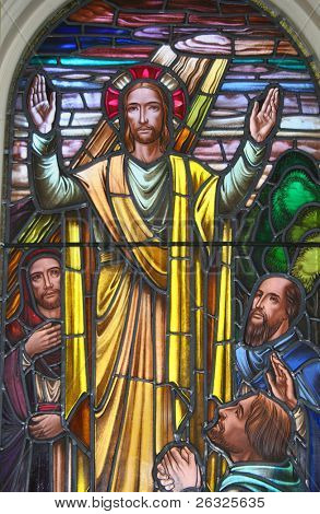 A stained glass pictorial of Jesus offering blessings.