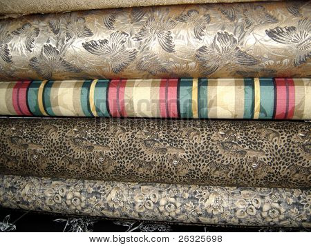 A variety of different bolts of fabric.