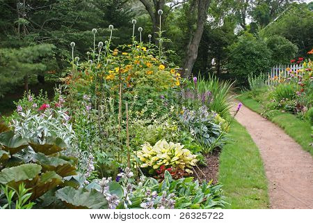 A path through a park surrounded by colorful perennial beds.