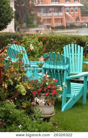 Rain falling on turquoise lawn chairs in a Bermuda garden.