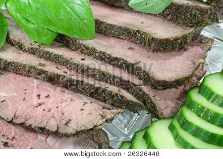 A platter of herb encrusted sliced roast beef done medium to medium rare.