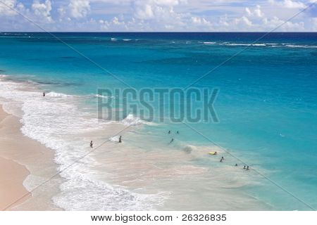 Swimmers in the ocean and enjoying the pink sand of Crane Beach on the beautiful Caribbean island of Barbados.
