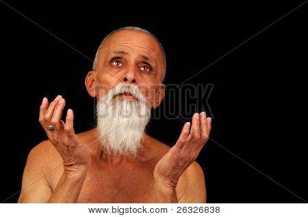 A senior man looking heavenward in a prayerful or pleading pose.
