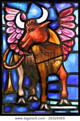 The winged ox is the evangelical symbol of St. Luke.  From an old stained glass window in an Anglican Church in Bermuda.