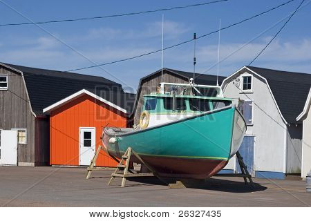 Commercial lobster boat outside colorful bait sheds prior to launching in the water in the spring.