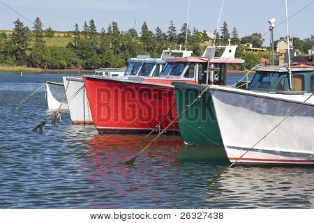 Commercial lobster fishing boats tied up off a wharf in Prince Edward Island, Canada.