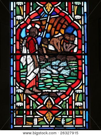 Stained glass window with fishermen disciples hauling in their nets full of fish.