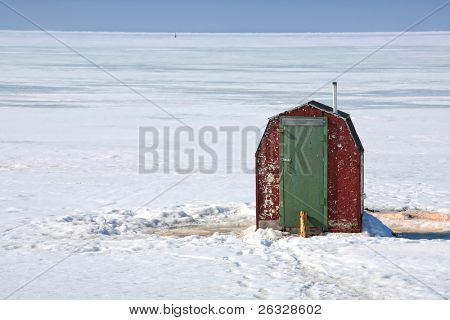 Rustic ice fishing shack out on the ice off Prince Edward Island, Canada.  Perfect for fishing smelts, a relative of mackeral.