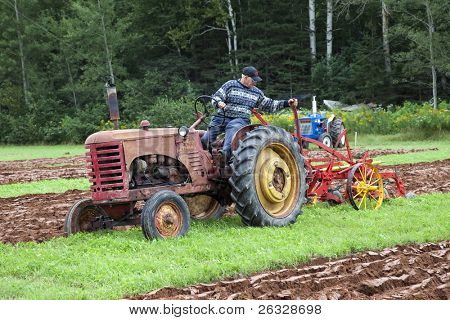 DUNDAS, P EDWARD ISLAND, CANADA-AUG 26:A competitor on an antique tractor competes in the plowing match at 71st annual Provincial Plowing Match & Agricultural Fair in Dundas, PEI on August 26, 2011