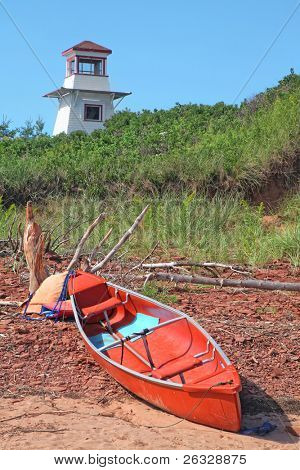 A canoe and some driftwood laying on the beach in front of the lighthouse at Cabot Beach in Malpaque, Prince Edward Island, Canada.