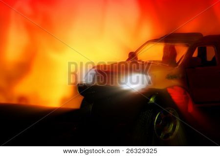 A car with lights on on the burning background