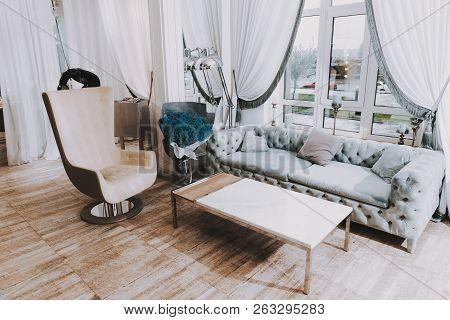 poster of Fashion Workplace. Blue Sofa And Big Window. Fashion Salon. Luxury Design. White Interior In Salon.