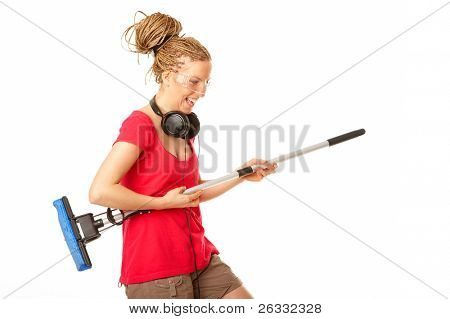 Young girl pretending to play the guitar on a mop, isolated against a white background