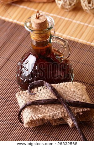 Vanilla extract with beans on natural background
