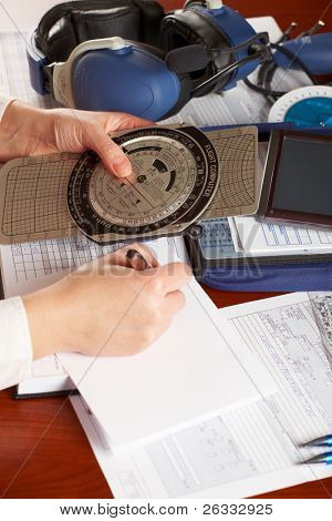 Pilot equipment with airplane pilot hands doing calculations, other tools like flight computer used for aviation calculations, protractor, kneepad with charts and professional headset