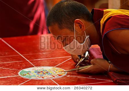 MCLEOD GANJ, INDIA - MAY 22: Buddhist monks making sand mandala on May 22, 2010 in McLeod Ganj, India.  This is a Tibetan tradition of creation and destruction of mandalas made from colored sand