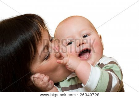 Young mother kissing her little smiling baby. Isolated on white background.