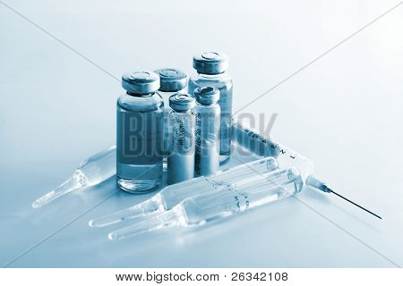 Flasks with medicines and syringe. Blue tone special FX