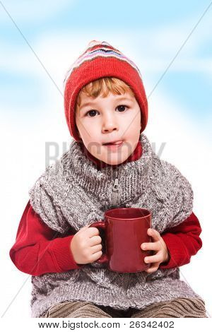 Cute little boy with red cup in his hands
