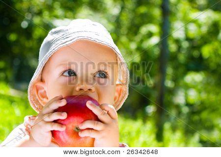 Retrato do lindo bebê menino comendo maçã no gramado