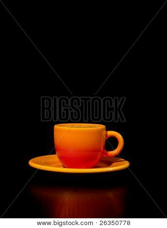 Vertical format side view of  cup of coffee against a black background with space for text