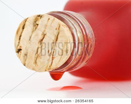 Pequena garrafa com um líquido vermelho isolado no branco