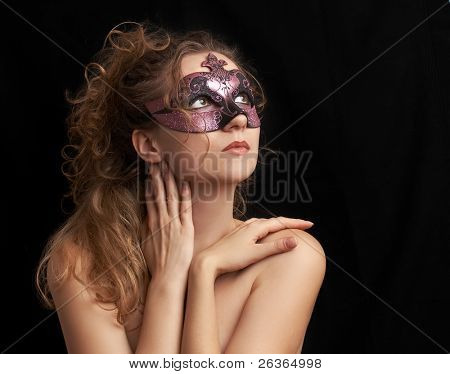 portrait of a sensual beautiful blond young woman with purple carnival mask, role play